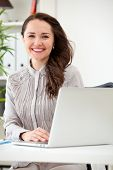 Smiling business woman working on laptop computer at office