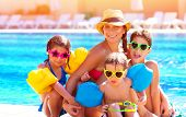 Happy big family having fun at the pool, spending summer vacation together, wearing funny colorful s