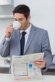 Businessman drinking a coffee and reading a newspaper before going to work