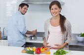 Cheerful pregnant woman holding her belly in the kitchen with her husband cooking behind