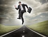 Businessman jumping on a road leading out to the horizon