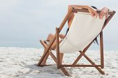 Woman lying on her deck chair on beach
