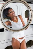 Portrait of happy young woman in undergarments looking through washing machine door