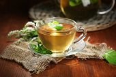 Cup and teapot of herbal tea with fresh mint flowers on wooden table