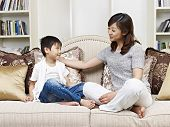 picture of crossed legs  - asian mother and son having a conversation on couch at home - JPG