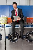 Full length of young businessman using digital tablet while sitting on washing machine in laundry