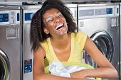 Closeup of cheerful young woman with laundry basket at laundromat