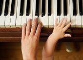 Adult Hand Playing Piano With Baby Hand