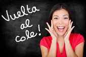 Vuelta al cole - Spanish student screaming Back to School written in Spanish on blackboard by woman teacher. Smiling happy woman teaching Spanish language or university student back in college.