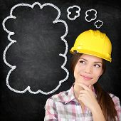 Thinking young female construction worker, architect, engineer, surveyor wearing hardhat on blackboa