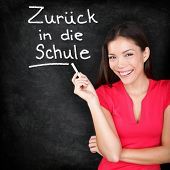 Zur�?�¼ck in die schule - German teacher Back to School written in German on blackboard by woman teacher holding chalk. Smiling happy woman teaching German language or university student back in college.