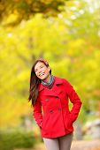 Fall woman walking amongst autumn trees. Beautfiul laughing young woman in a trendy red jacket walking amongst colourful yellow autumn trees with copy space. Mixed race Chinese Asian / Caucasian girl.