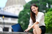 Business people - laptop woman in Hong Kong. Business woman on computer and internet outside in Central Hong Kong. Young female professional businesswoman smiling happy. Asian Chinese Caucasian woman.