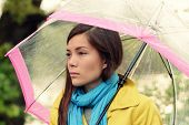 Melancholia - Melancholic woman in rain under umbrella looking sad unhappy and thoughful. Pretty gir