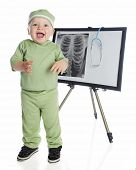 An adorable baby boy in green scrubs laughing as he stands before an easel displaying a human chest x-ray and stethoscope.  On a white background.