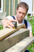 Handsome Handyman Measuring Wooden Plank Outdoors
