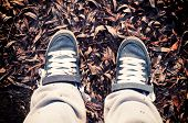 stock photo of snickers  - Dirty jeans snickers on foot from above - JPG