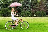 Young Woman Riding A Bicycle In A Park Holding A Pink Umbrella