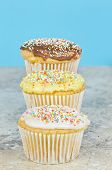 stock photo of three tier  - Three cupcakes tiered with different toppings on a tile with a blue background - JPG