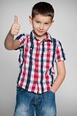 Young Boy Holds His Thumb Up On The Grey Background