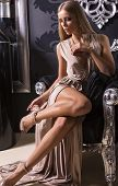 beautiful woman with long legs in beige silk dress sitting on the black armchair