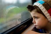 stock photo of stare  - a boy in a train staring through a window - JPG