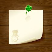 Wooden background with paper and clover