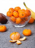 Fresh Clementines fruit peeled with glass bowl in vertical
