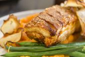 stock photo of pork belly  - Delicious roasted pork belly with crackling sweet potato mash and steamed green beans.