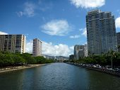 picture of waikiki  - Ala Wai Canal hotels Condos and trees on a nice day in Waikiki on Oahu Hawaii with mountains in the distance - JPG