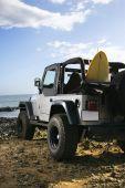 SUV und Surfbrett am Strand