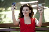Young woman with two smartphones catches Wi fi in the park