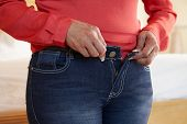 Close Up Of Overweight Woman Trying To Fasten Trousers