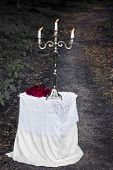 Silver Candlestick On A White Table With A Red Roses In A Forest On A Footpath