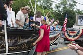 Man shucks oysters on a float in the Wellfleet 4th of July Parade in Wellfleet, Massachusetts.