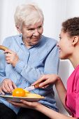 Nurse And Elderly Woman Eating Fruits