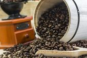 Scattered Roasted Coffee Beans On Wooden Ladle From Wooden Barrel