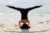 Woman in a headstand head stand on the beach