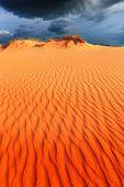 Scene with dunes in sand desert under dark sky before thunder storm