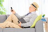 Senior gentleman sending an sms via cell phone at home