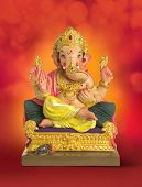 A sculpture of an Indian god Lord Ganesha on bright red background