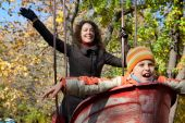 Mother with son shake on swing in autumnal park