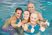Happy family with senior couple in swimming pool holding thumbs up