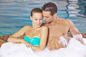 Happy couple in their holidays relaxing in a whirlpool of a hotel