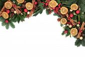 Christmas background border with cinnamon spice, dried orange fruit, bauble decorations, holly and w
