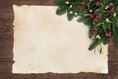 Winter and christmas background border of fir, mistletoe and pine cones over old parchment paper and
