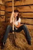 Portrait of girl in white shirt and blue jeans on pile of straw in hayloft. Vertical format