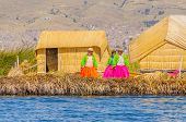 PUNO, PERU, MAY 5, 2014 - Women in traditional attires welcome tourists coming by boats from Puno town to visit floating Uros islands on Lake Titicaca