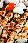 grilled and raw chicken shish kebab cooked on barbecue appliance