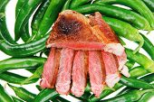 meaty food : grilled red meat steak sliced on a green hot chili peppers on a white back background